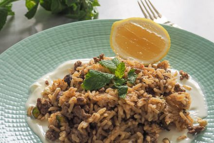 Dish of lamb and rice with lemon and mint in background
