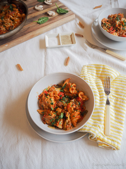 one pan baked vegetable pasta in bowl and pan on white tablecloth